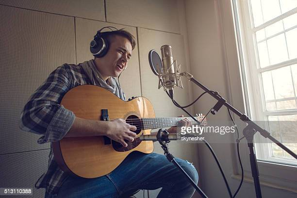 Young man playing acoustic guitar and singing in recording studio.