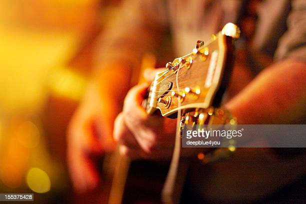 young man playing acoustic guitar in concert - blues music stock pictures, royalty-free photos & images