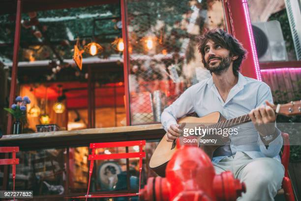 young man playing acoustic guitar - pop musician stock photos and pictures