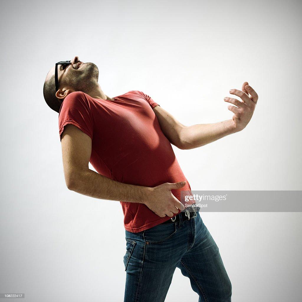 Young man playing air guitar : Stock Photo