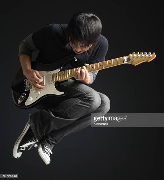 Young man playing an electric guitar