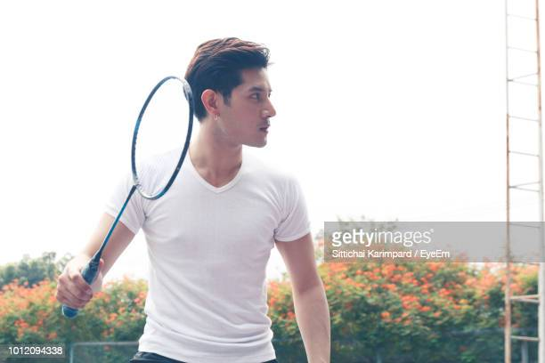 young man playing badminton against clear sky - スポーツ バドミントン ストックフォトと画像