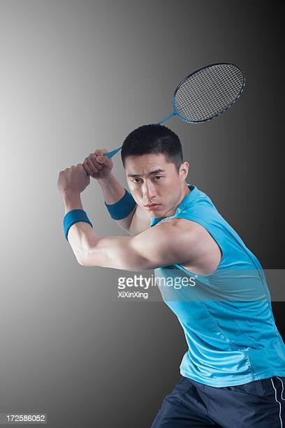 Young man playing badminton, racket raised