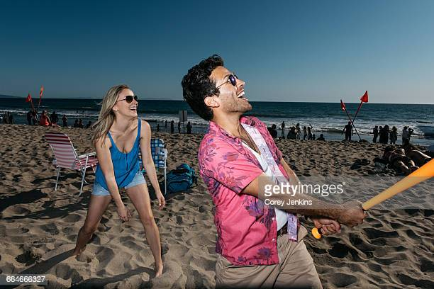 Young man playing baseball on beach, Santa Monica, California, USA
