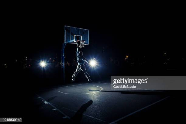 young man playing basketball at night - segnare foto e immagini stock