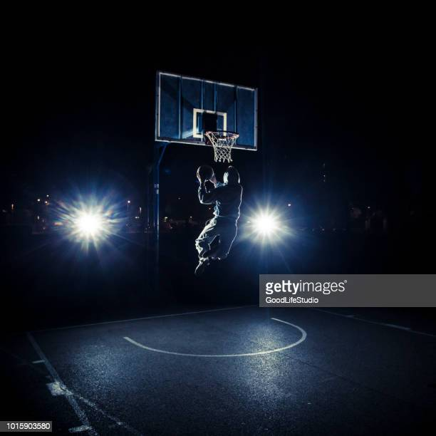 young man playing basketball at night - traditional sport stock photos and pictures