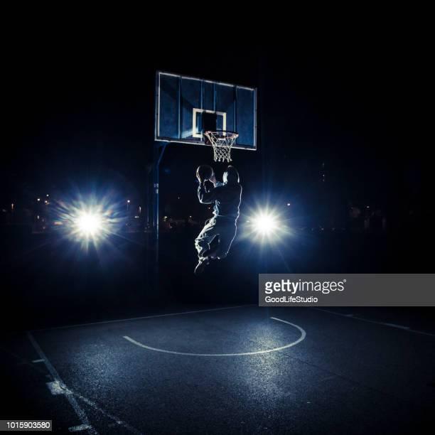 joven jugando baloncesto en la noche - encestar fotografías e imágenes de stock