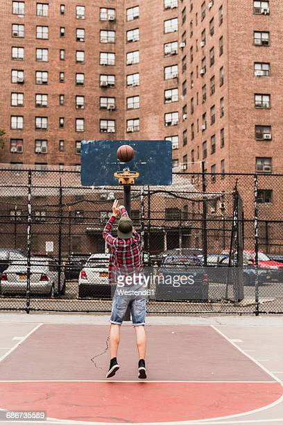 young man playing basketball on an outdoor court - shooting baskets stock pictures, royalty-free photos & images