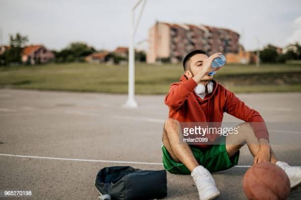 Jeune homme jouant au basketball sur son terrain favori