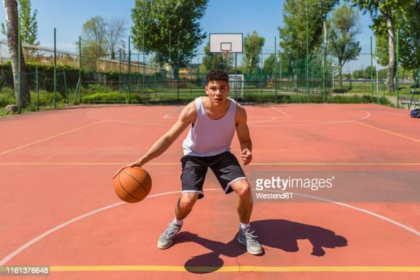young man playing basketball - bouncing stock pictures, royalty-free photos & images