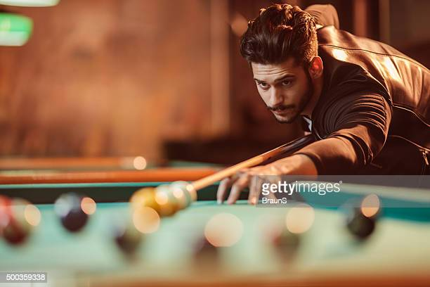 Young man playing billiard in a pool hall.