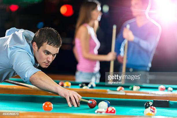 Young man playing billiard.