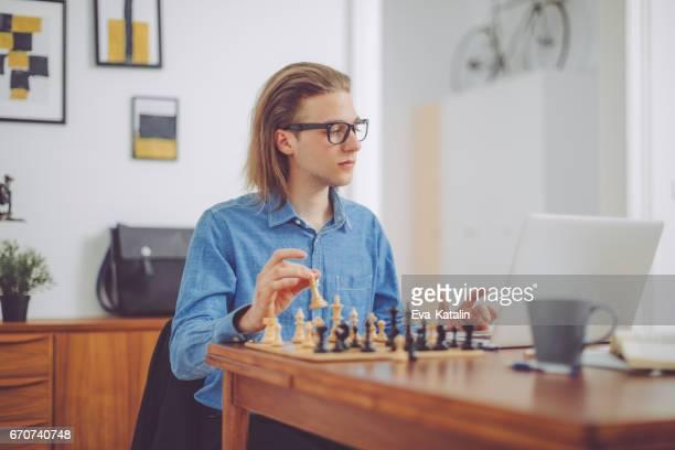 Ung man spelar schack hemma
