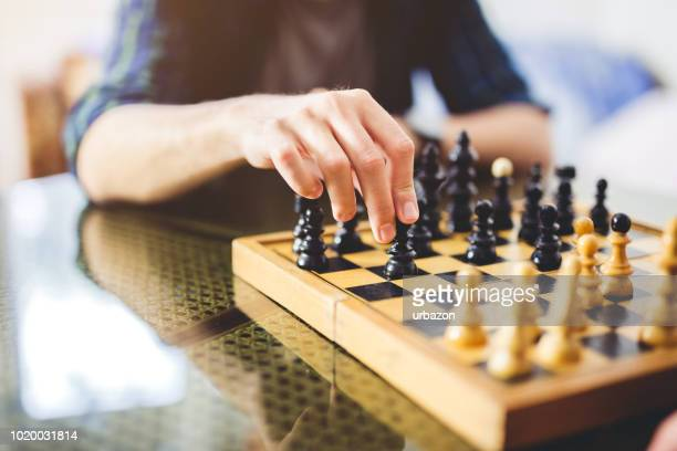 young man playing chess - chess stock pictures, royalty-free photos & images