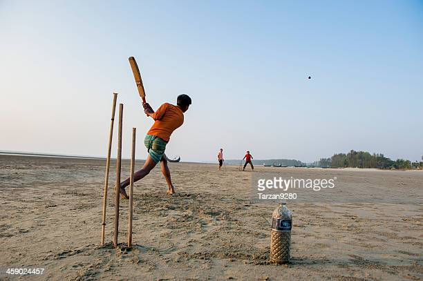 young man playing cricket on the beach, bangladesh - bangladesh cricket stock photos and pictures