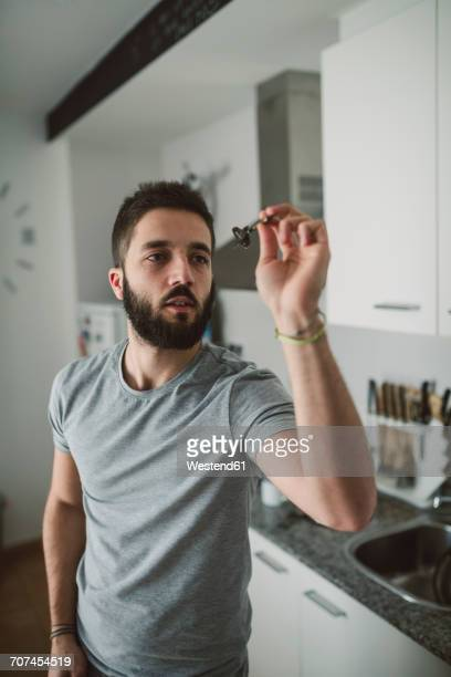 Young man playing darts in his kitchen