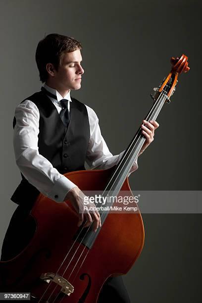 Young man playing double bass, studio shot