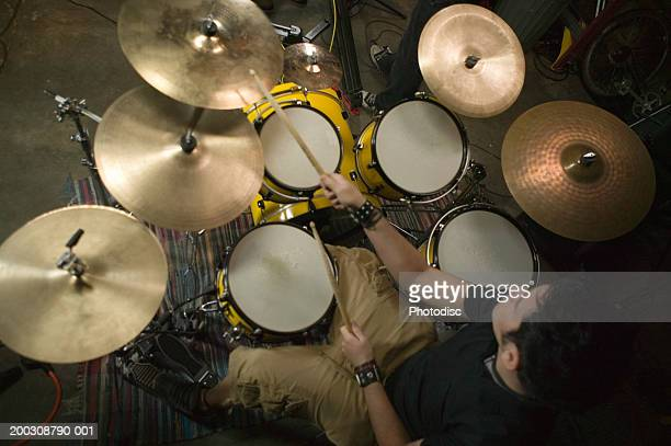 Young man playing drums, elevated view