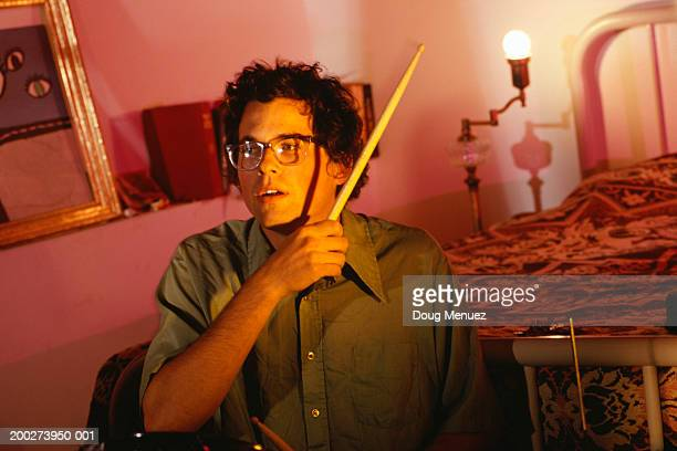 Young man playing drums in bedroom