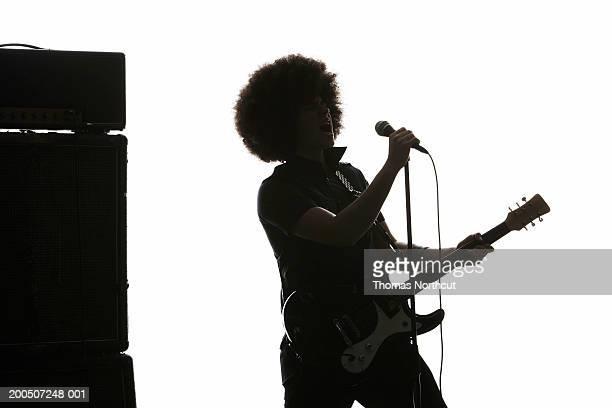jeune homme jouant de la guitare électrique et chante dans un microphone - guitariste photos et images de collection