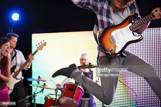 Young man playing electric guitar jumping in air