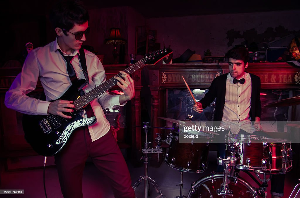 Young man playing electric guitar on club concert : Stock Photo