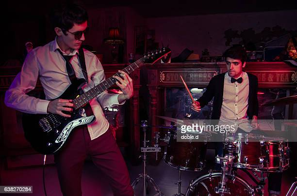 Young man playing electric guitar on club concert