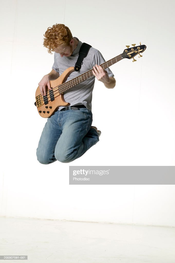 Young Man Playing Electric Guitar Posing In Studio Portrait Stock Photo
