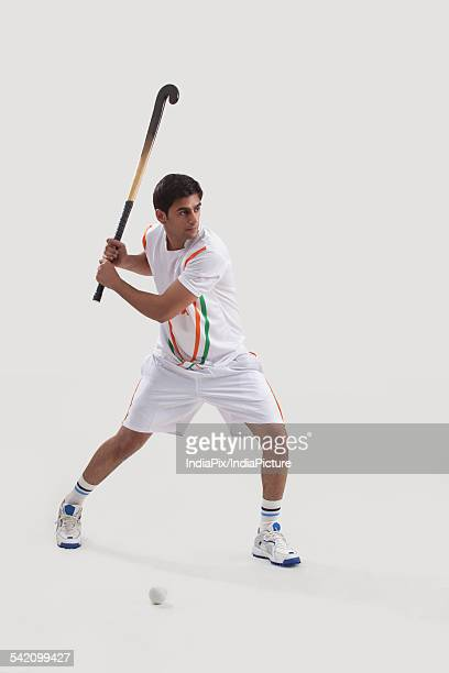 Young man playing field hockey isolated over white background