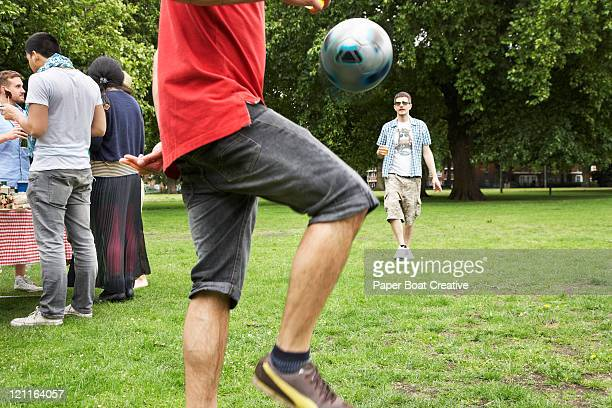 young man playing football in park - driblar esportes - fotografias e filmes do acervo