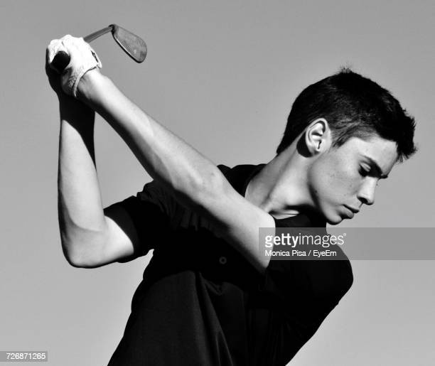 young man playing golf against clear sky - ゴルフのスウィング ストックフォトと画像