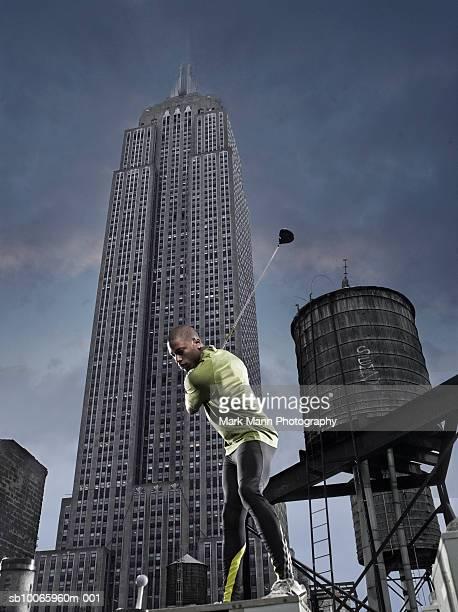 junger mann spielt golf in street, wolkenkratzer in hintergrund, low - golf lustig stock-fotos und bilder