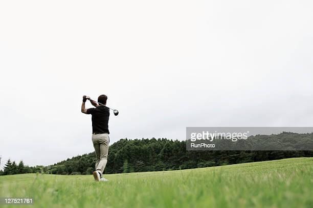 young man playing golf,back shot - ゴルフクラブ ドライバー ストックフォトと画像