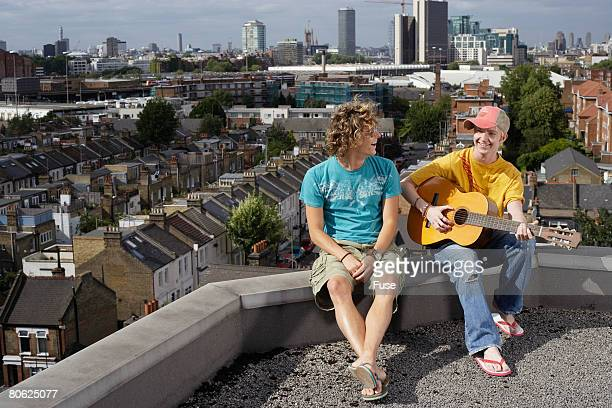 Young Man Playing Guitar for Friend