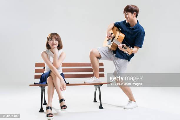 Young man playing guitar for his girlfriend
