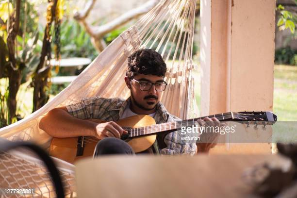 田舎でギターを弾く若者。 - 爪弾く ストックフォトと画像