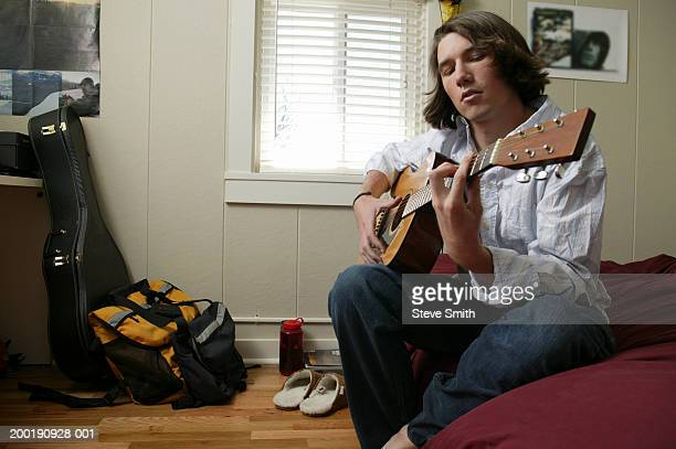 Young man playing guitar in bedroom