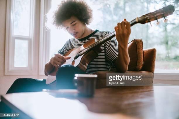 若い男リビング ホームでギターを弾く - シンガーソングライター ストックフォトと画像
