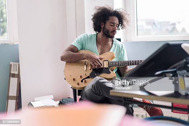young man playing guitar in office - gitarre stock-fotos und bilder