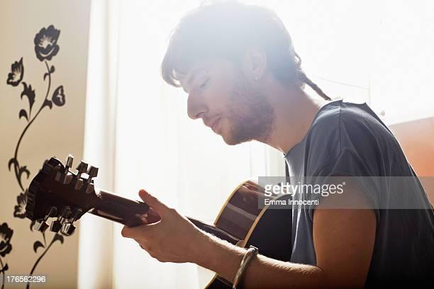 Young man playing guitar indoors