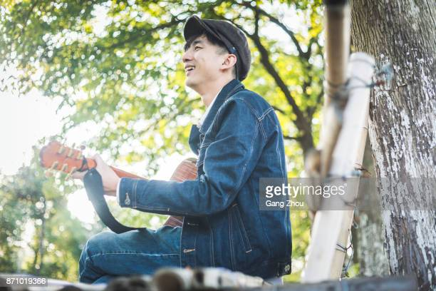 young man playing guitar on park bench - acoustic guitar stock pictures, royalty-free photos & images