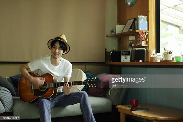 Young man playing guitar on sofa in living room