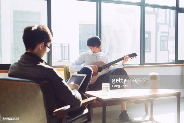 young man playing guitar on sofa while his friend using tablet PC