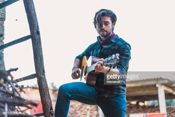 young man playing guitar outdoors on a farm - guitarist stock pictures, royalty-free photos & images