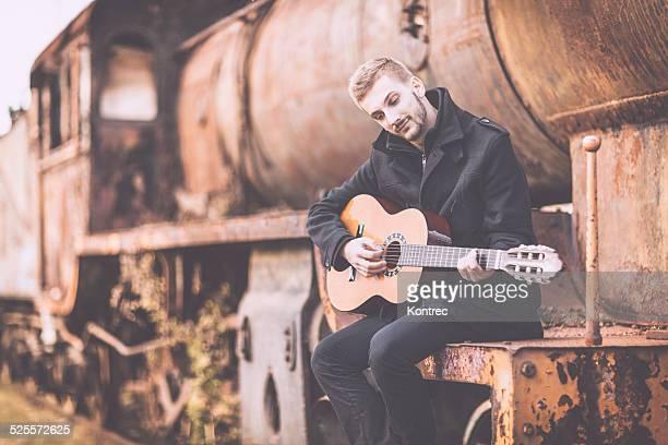 Junger Mann spielt Gitarre im Freien