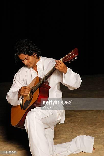 A young man playing guitar