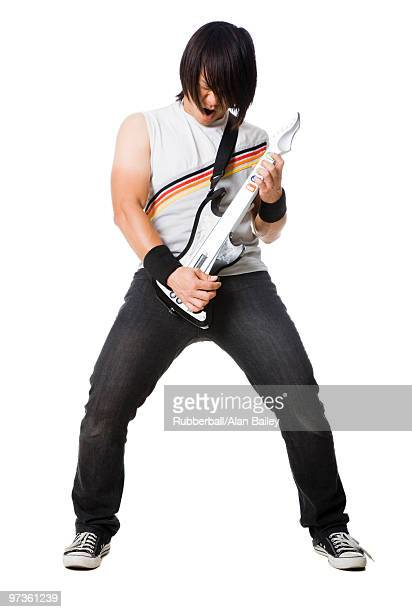 young man playing guitar video game and screaming, studio shot - guitar hero stock photos and pictures
