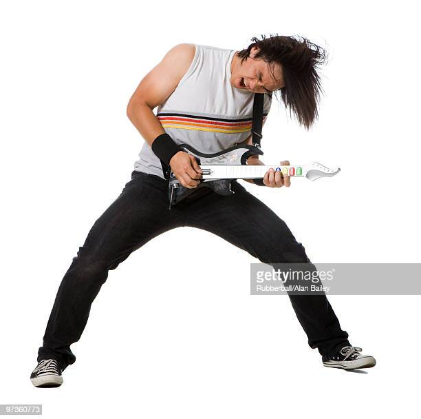 young man playing guitar video game and singing, studio shot - guitar hero stock photos and pictures