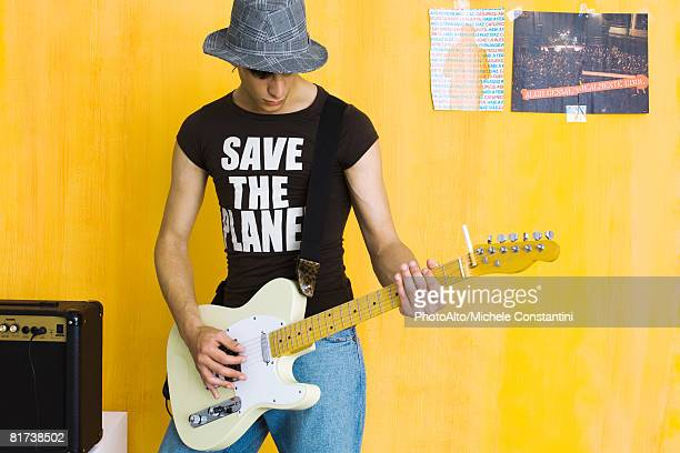 Young man playing guitar, wearing save the planet tee-shirt