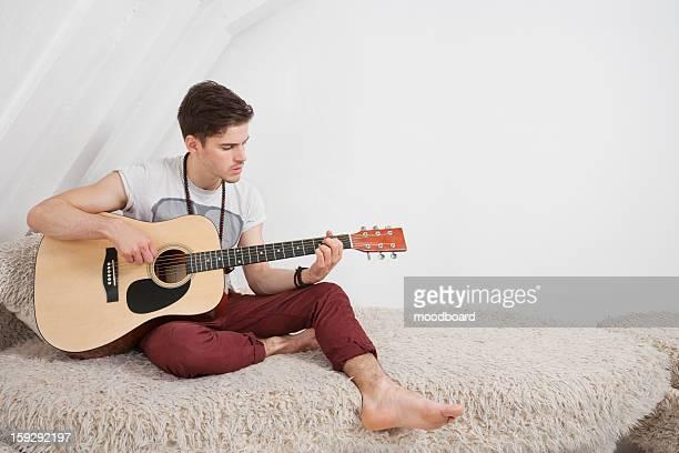 Young man playing guitar while sitting on fur sofa